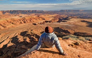 USA, Utah, Canyonlands National Park, Hiker looking at Buck Canyon
