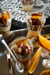 Tiramisu in glasses and slices of orange