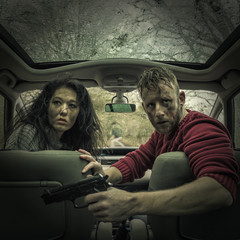 Man and woman in car with handgun