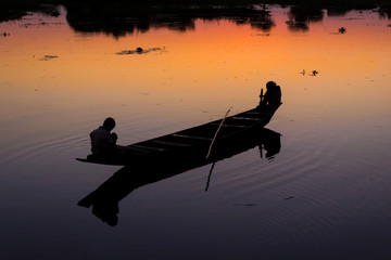 Silhouette of people in fishing boat