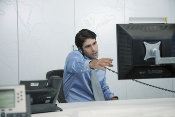 Man using phone in office and pointing at computer monitor