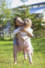 Iceland, Girls (2-3, 10-11) hugging in meadow