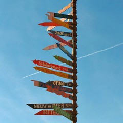 Multi colored directional signs against blue sky