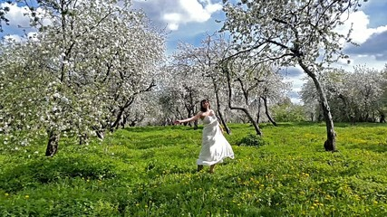 Young woman having fun in the blooming apple garden. Slow speed