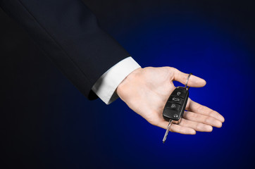 car salesman in a black suit holds the keys to a new car studio