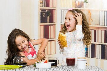 Two young preschooler girls eating at the table