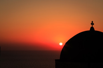 Sun setting over a church in Oia village, Santorini.