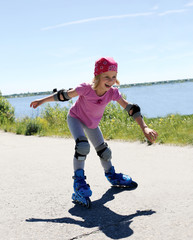 Little girl is learning to roller skate. Girl happily rolling on