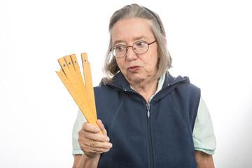 Alte Frau mit Zollstock schaut verzweifelt
