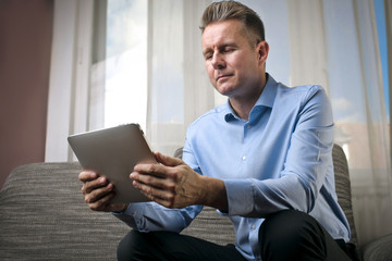 Businessman reading something on a tablet
