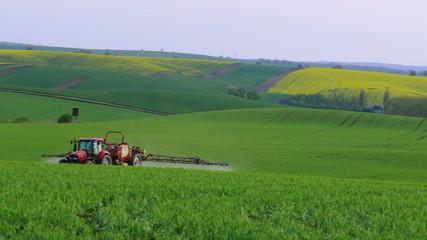 Evening hilly field. Tractor spray fertilizer