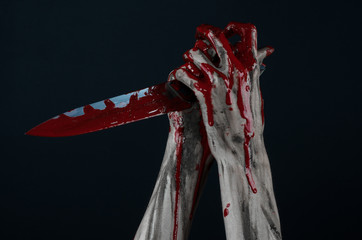 zombie killer holding a large bloody knife isolated  in studio