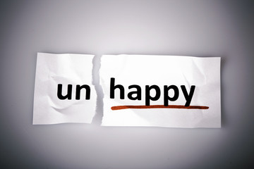 The word unhappy changed to happy on torn paper