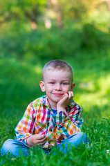 A little boy sitting on the grass, smiling and head support arm