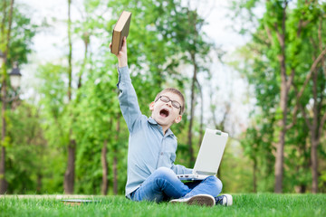young surprised boy with a books and laptop
