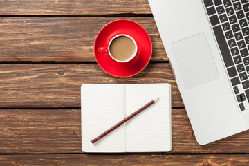 Cup of coffee and notebook with laptop computer