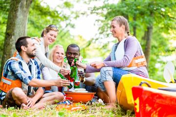 Freunde grillen nach Sport im Wald und trinken Bier