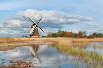 Dutch windmill by river and blue sky