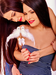 Lesbian women with dove in erotic foreplay game