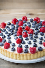 Cake with blueberries and raspberries. Confectionery product.
