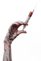 bloody hands of the doctor holding a bloody syringe