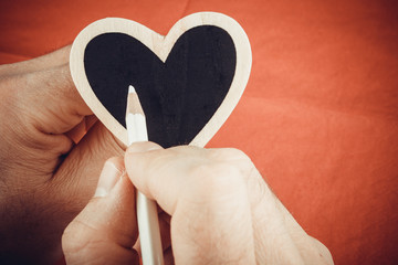hand writing on the wooden heart for Valentine's day