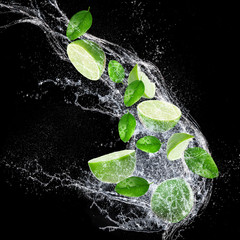 Ripe limes with water splash