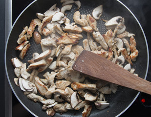 Chicken fillet frying on pan with mushroom