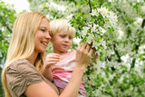 Mother and Young Child Looking at Flowering Crabapple Tree