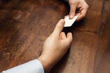 mani che si scambiano un bigliettino da visita