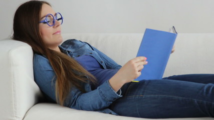 Woman lying on couch reading book at home. Full HD