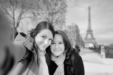 Two young woman taking a selfie near the Eiffel tower
