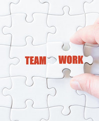 Missing jigsaw puzzle piece with word TEAMWORK