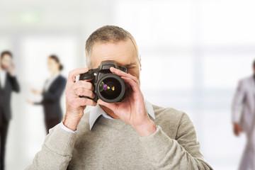 Mature photographer with camera.