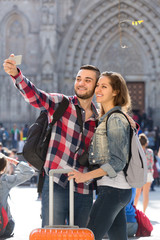 Couple with luggage doing selfie