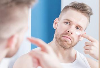 Guy applying facial cream