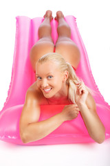 Blond female lying on pink matress