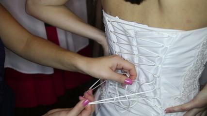 bridesmaid ties corset on bride wedding dress close up
