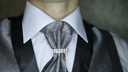 groom in silver vest corrects brooch on dark silver necktie
