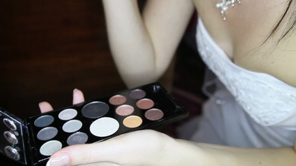 young bride in white wedding dress does stylish makeup