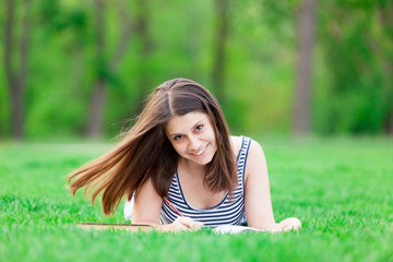 girl with book on the green grass