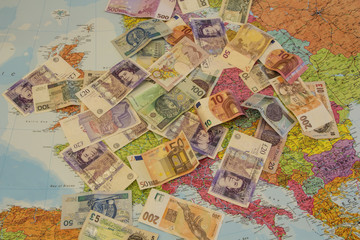 Four different currencies laid out on the map of Europe