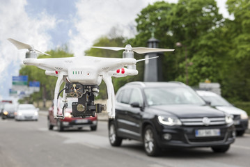 Flying drone with camera beside a road