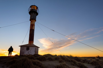 Man outside patagonia lighthouse at sunset