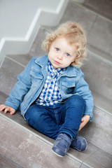 Blond baby sitting on the stairs at home