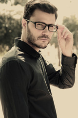 handsome man wearing a pair of glasses posing outdoors