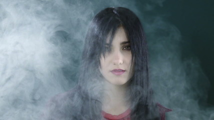 Portrait of beautiful woman coming out from the fog in studio