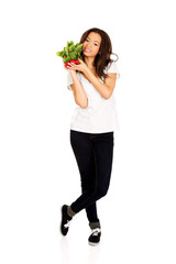 Young woman with bunch of radishes.