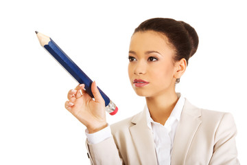 Businesswoman pointing up with big pencil.