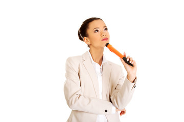 Thoughtful businesswoman with big pen.